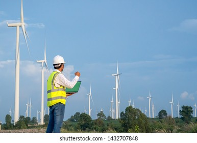 Wind Turbine Asian Mechanical Engineer working by laptop computer at Wind Turbine field,wind power and Alternative energy concept,Electric power industry.success happy pose