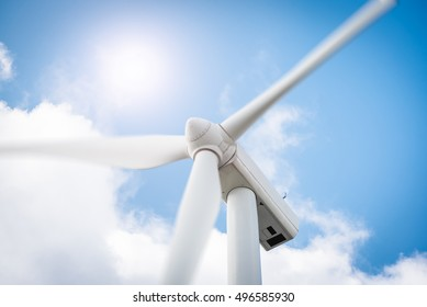 Wind turbine close up in eolic park generating energy with air flow with spinning blades in a natural blue sky background. Clean renewable green wind power concept.