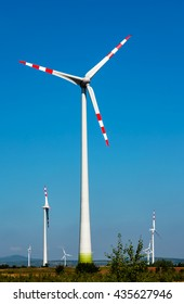 Wind turbine electric power generator in the filed in Germany on blue sky