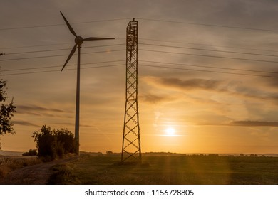Wind turbine and electricity power line in sunrise. Sustainable development environment friendly concept