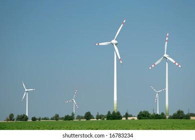 Wind turbine farm on a green field. Alternative source of energy.