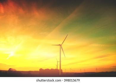 Wind turbine farm with rays of light at sunset