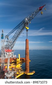 Wind Turbine foundation installation by a large crane vessel in the North Sea, off the Norfolk coast