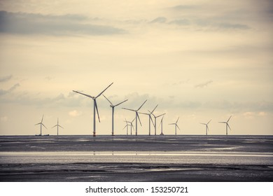wind turbine generating electricity at the mud flat near sea shore