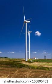 Wind turbine generating electricity on blue sky background