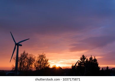 Wind turbine generator at beautiful sunset. Ecological air energy.