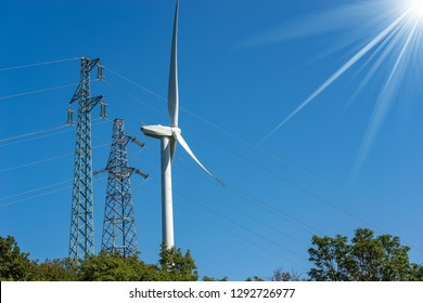 Wind turbine and high voltage towers (power line) on a clear blue sky with sun rays - Renewable energy concept