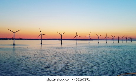 a lot of wind turbine in the middle of sea with a beautiful sunset