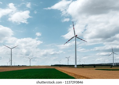 Wind turbine on agricultural field against blue sky background