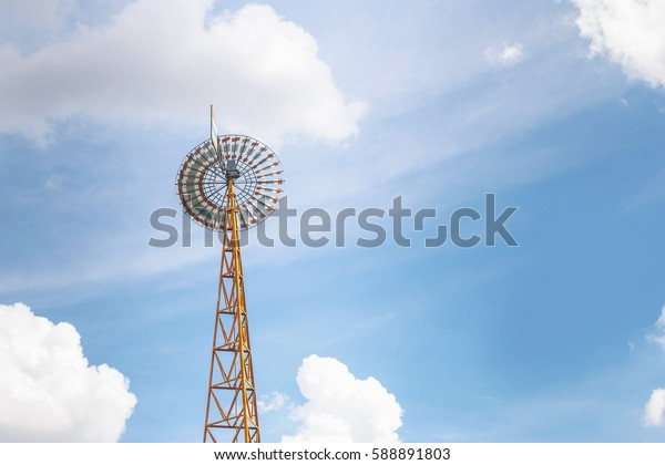 Wind turbine on blue sky. And fluffy white clouds