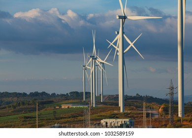 Wind turbine on mountain with blue sky background at sunset.