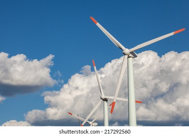 Wind turbine over the blue clouded sky
