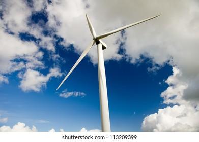 Wind turbine over the deep blue clouded sky