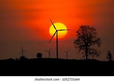 Wind turbine power generator on sunset.