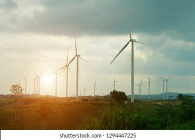 Wind turbine power generators silhouettes with sunset background.