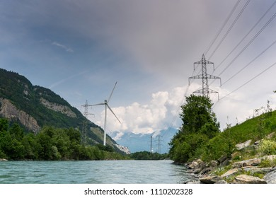 wind turbine and power lines on the banks of a river in a mountain valley