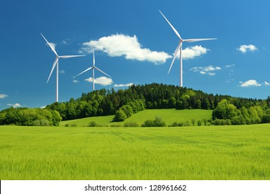 Wind turbine renewable energy source summer landscape with clear blue sky and field in the foreground