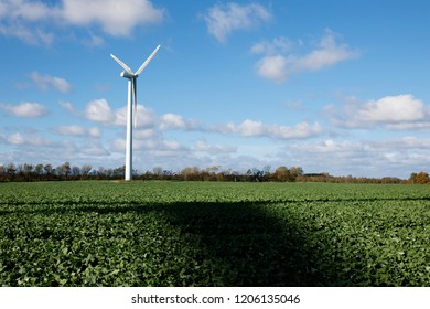Wind turbine shadow flicker in green field. Blue sky