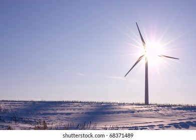 Wind turbine shot against the sun on the clear blue winter day. Concept picture for renewable energy; rule of thirds, closed aperture.