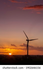 wind turbine silhouetted against a beautiful sunset. Portrait view. High quality photo