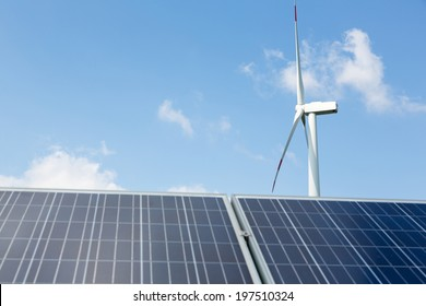 A wind turbine and solar panels with blue sky