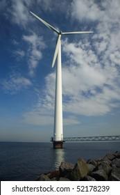 Wind turbine standing in the sea under a blue sky