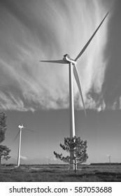 wind turbine windmill in rural area of atlantic coast rising up in blue sky and clouds in black and white isolated, algarve, portugal