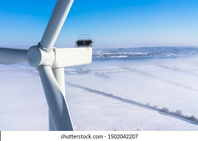 Wind turbine in winter with snow and fog Aerial view and close-up view