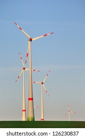 Wind turbines against blue sky.