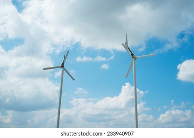 Wind turbines against a blue sky with clouds
