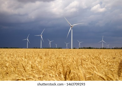 Wind turbines and agricultural field on a summer cloudy day. Energy production, clean and renewable energy.