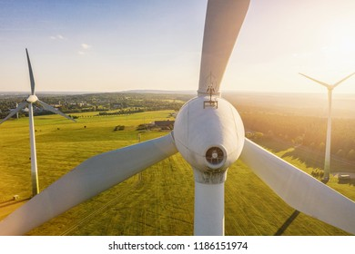 Wind turbines and agricultural fields on a summer day - Energy Production with clean and Renewable Energy - aerial drone shot