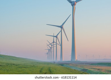 Wind turbines along a dike at dawn in spring