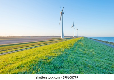 Wind turbines along a dike at sunrise