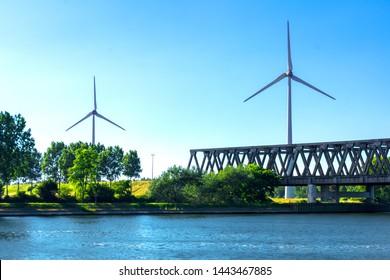 Wind turbines beside a bridge