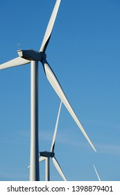 Wind turbines close up against a clear blue sky.