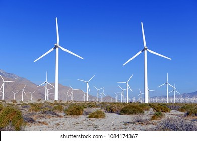 Wind turbines creating renewable energy on windfarm in desert with mountain background, a technology to move away from fossil fuels