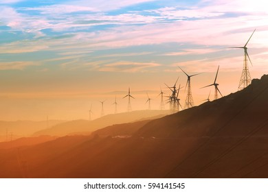 Wind turbines during sunset with Andalusian hills, Atlantic ocean and mountain of Africa on background.
