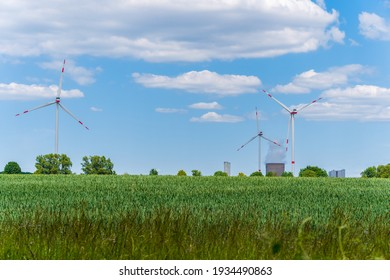 Wind turbines and electric power plant with smoking chimney in beautiful landscape with lush green agricultural wheat field and blue sky with clouds. Sustainable energy and environment concept.