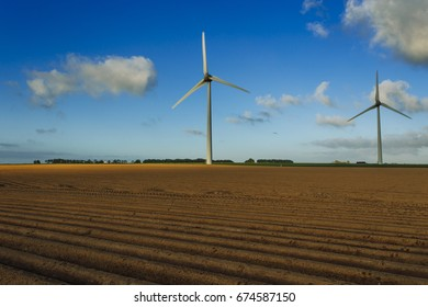 Wind turbines for electricity generation in agricultural field on a cloudy day in Normandy, France. Renewable energy sources, industrial agriculture concept. Environmentally friendly energy production