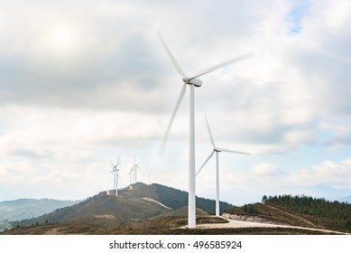 Wind turbines farm in eolic park generating energy with air flow with spinning blades in a rural setting. Clean renewable green wind power concept.