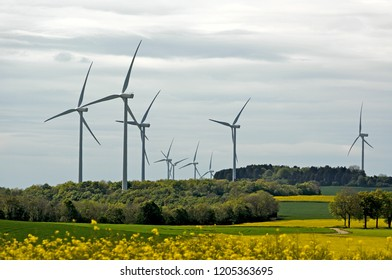 Wind turbines farm generating clean power in field in rural country.