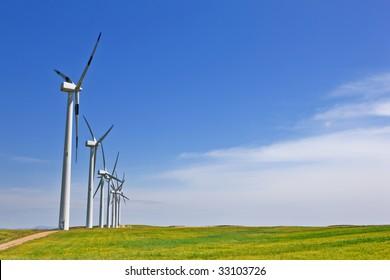 Wind turbines farm in green field over cloudy sky