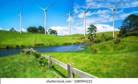 Wind turbines farm on a green grass rolling hills against blue sky and white clouds in summer. Concept of renewable clean energy and sustainability development business from wind energy.