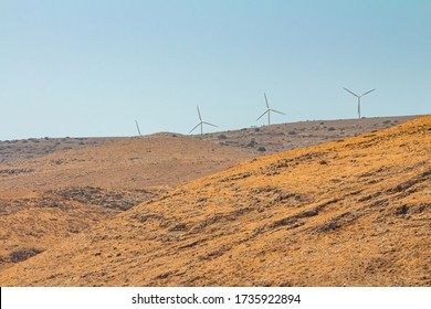 Wind turbines at a wind farm on a mountain in the Israeli Golan Heights. Dry summer day time. Long view with copy space.