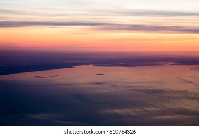 Wind turbines farm on North Sea at English coast view from sky in sunset light. Horizontal crop with top orange violet horizon.