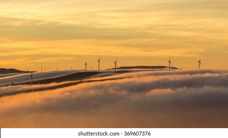 wind turbines farm over clouds at sunrise morning