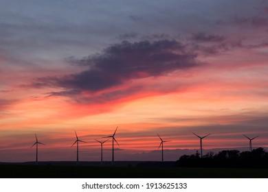 Windturbinen auf dem Feld, Deutschland, bei Sonnenuntergang. Eine Windturbine ist ein Gerät, das die kinetische Energie des Windes in elektrische Energie umwandelt. Es ist ein Symbol für Energiewende.
