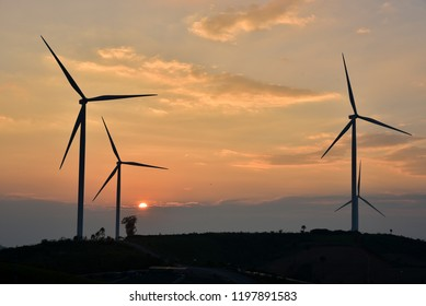 Wind turbines in a field in the UK at sunset or sunrise against a clear winter sky Beautiful sunset above the windmills on the field.