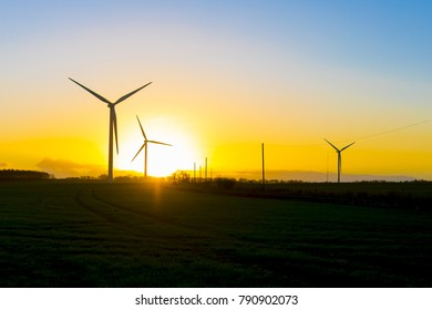 Wind turbines in a field in the UK at sunset or sunrise against a clear winter sky
